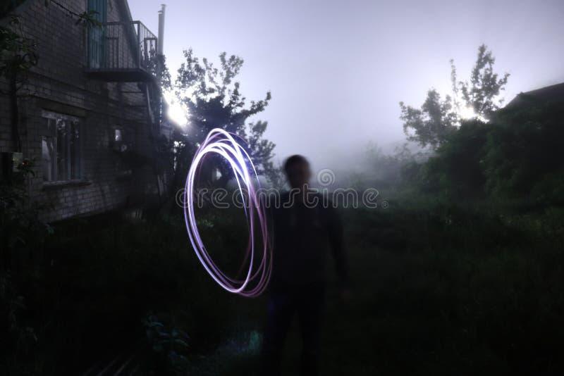 La figura pintura del hombre extraño con la luz en la oscuridad con el fondo de la niebla al aire libre imágenes de archivo libres de regalías