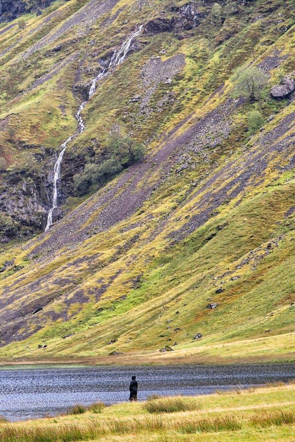 La figura solitaria se coloca al borde del lago Achtriochtan, Glencoe, Escocia foto de archivo