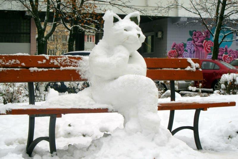 La figure d'un chat énorme moulé hors de la neige sur un banc de ville à Kiev images stock