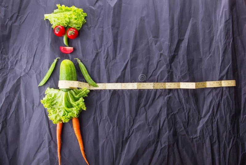 La figure de la fille avec des légumes sur le fond de papier noir Perte de poids et mode de vie sain Avec l'espace pour le texte image stock