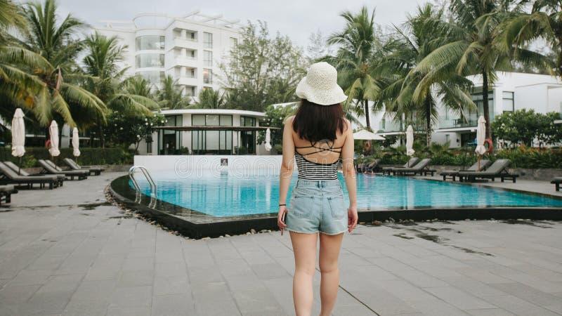 La figure femelle marche vers une piscine photos stock