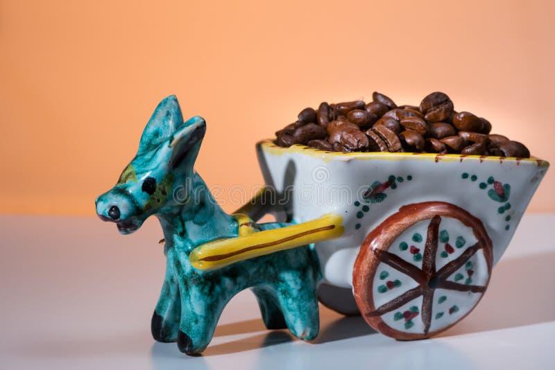 La figurina di un asino ceramico che tira un carretto ha riempito di caffè b immagini stock