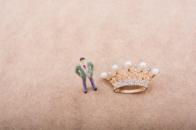 La figurina ed il colore dorato coronano il modello con le perle false immagini stock libere da diritti