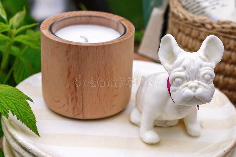 La figurine en céramique d'un petit bouledogue français se tient d'un plat avec une bougie photographie stock
