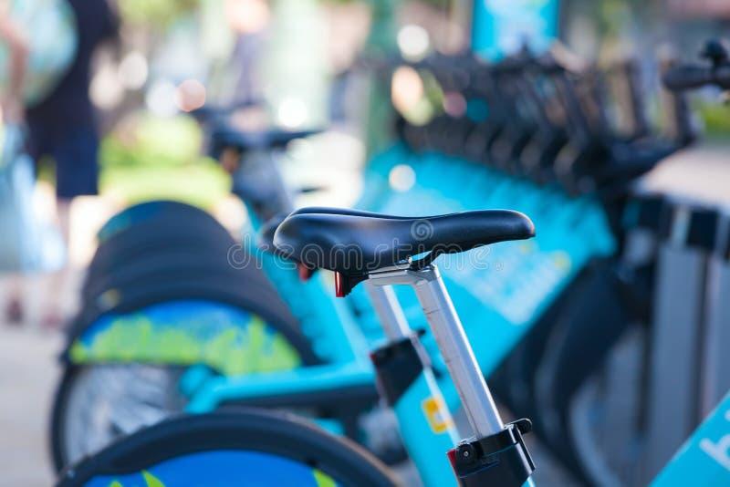 La fila de bicis azules parqueó en la acera de la ciudad fotos de archivo