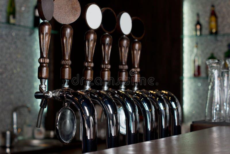 La fila de la cerveza golpea ligeramente en un barrilete del acero inoxidable en un pub imágenes de archivo libres de regalías