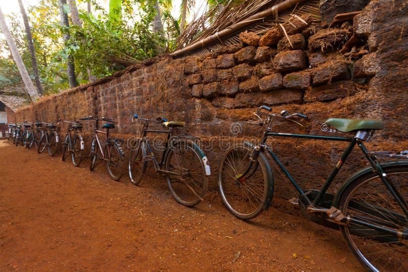 La fila de la India monta en bicicleta el camino de tierra de la pared de piedra fotos de archivo