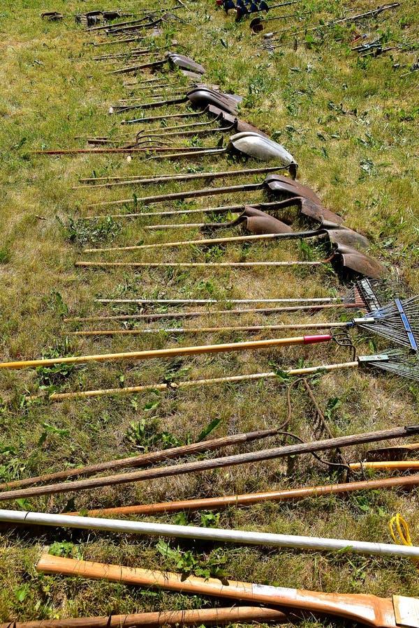 La fila de las espadas, de las palas, de las bifurcaciones, y de la madera de la subasta manejó las herramientas fotografía de archivo