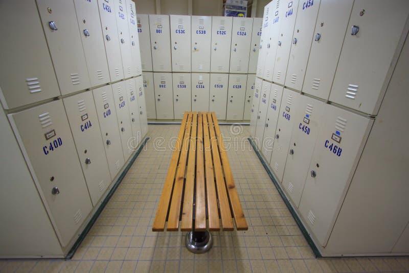 La fila de los armarios de acero a lo largo de la silla, vestuario para el trabajador en sitio del trabajo, mantiene pertenecer p imágenes de archivo libres de regalías
