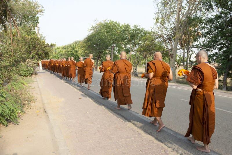 La fila de unidentify a los monjes que caminan para recoger limosnas y ofrendas por la mañana en BUDA GAYA, la INDIA fotos de archivo