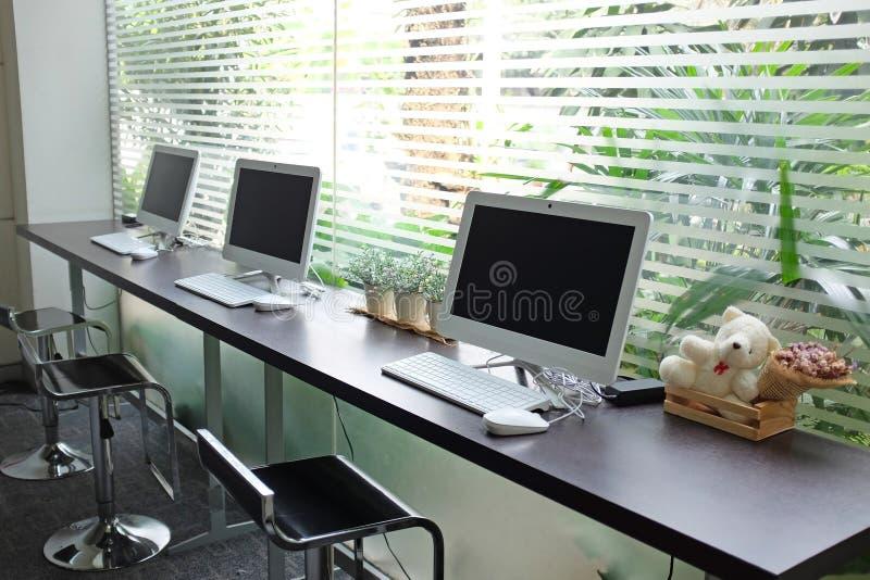 La fila dei computer che aspettano la gente usa al cybercaffè immagini stock libere da diritti