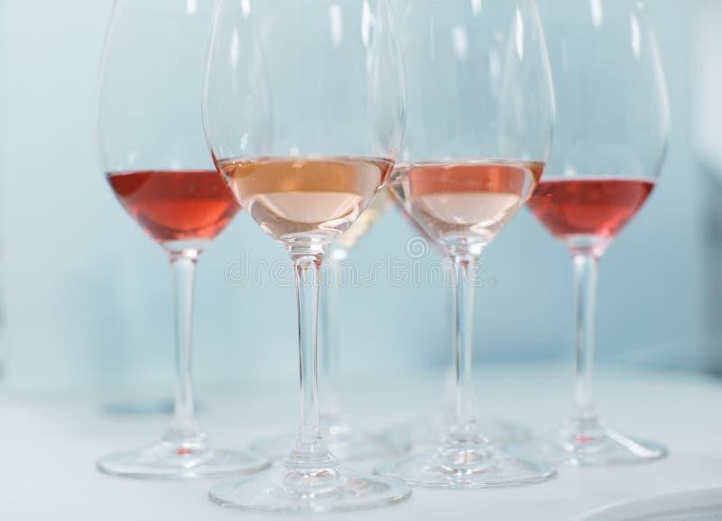 La fila dei vetri con bianco e dei vini rosati ha preparato per il degustatio immagini stock libere da diritti