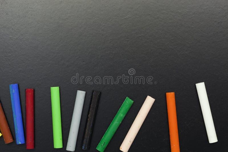 la fila del arco iris coloreó tiza en fondo de la pizarra imágenes de archivo libres de regalías