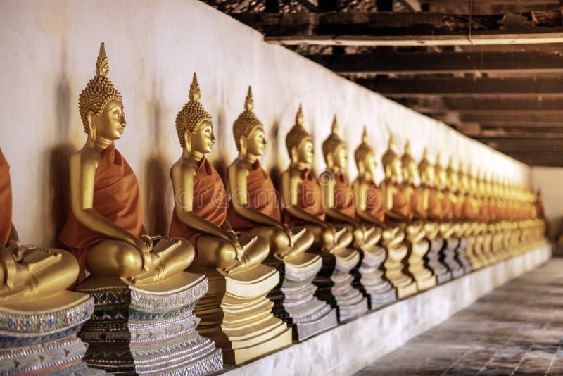 La fila delle figure di seduta statue di Buddha di meditazione dorata dentro il corridoio è allineata a Wat Phutthaisawan, si Ayu fotografia stock libera da diritti