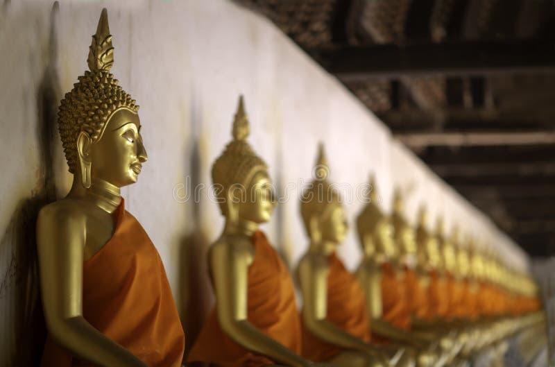 La fila delle figure di seduta statue di Buddha di meditazione dorata dentro il corridoio è allineata a Wat Phutthaisawan, si Ayu fotografia stock