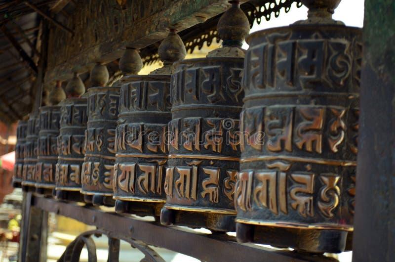 La fila delle ruote buddisti dei tamburi di preghiera arriva a fiumi il tempio di Swayambhu Swayambhunath immagini stock libere da diritti