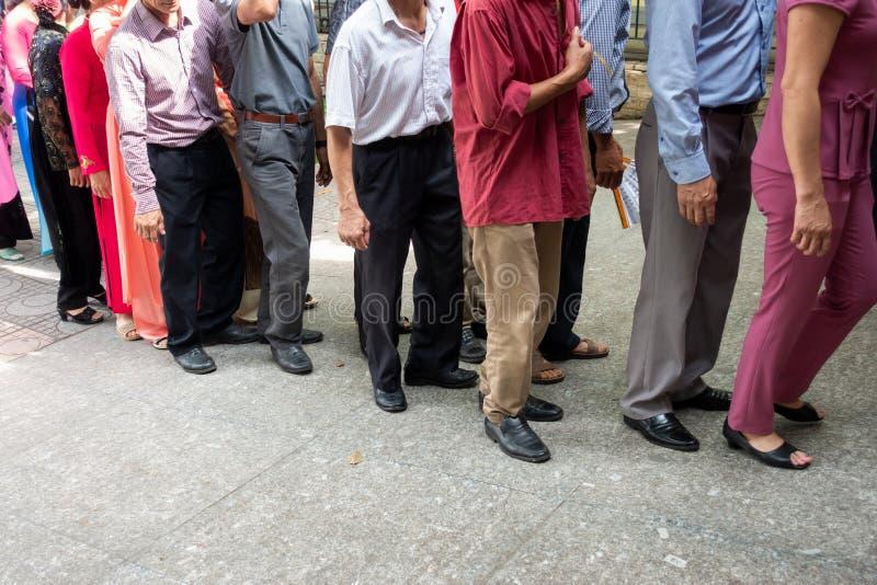 La file d'attente des personnes asiatiques attendent dans la ligne dans la rue urbaine photo stock