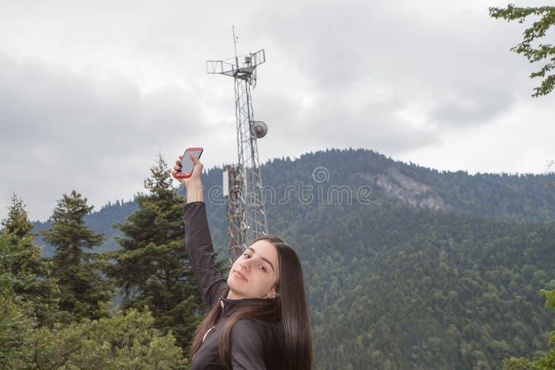 La fille à l'aide du téléphone portable avec la télécommunication domine avec les antennes de TV et l'antenne parabolique image libre de droits