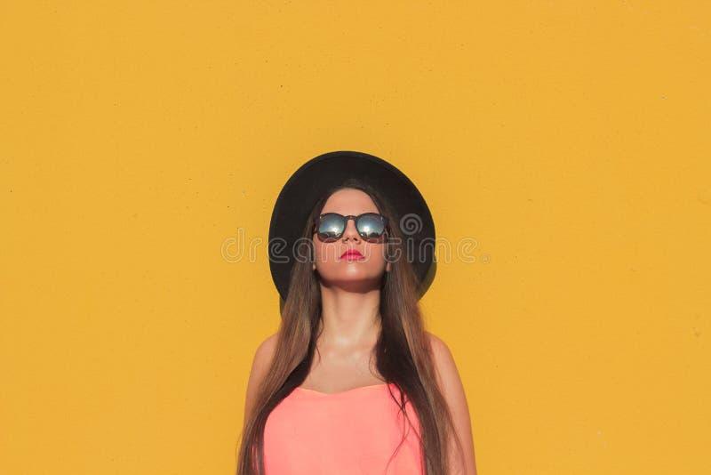 La fille à la mode avec les lunettes de soleil et le chapeau noir avec un mur jaune comme fond photos stock