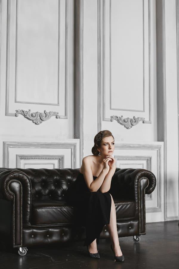 La fille à la mode et élégante de modèle de brune avec de grandes boucles d'oreille douces de maquillage et de witj, dans la long images stock
