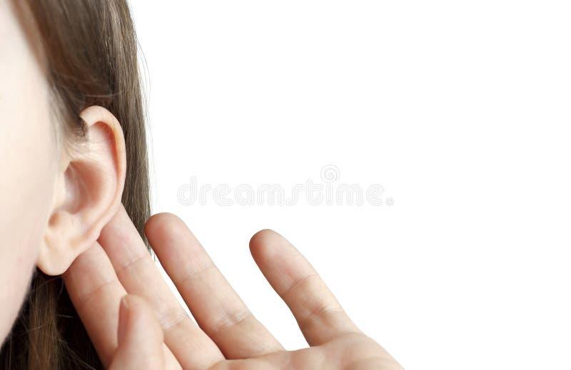 La fille écoute attentivement avec sa paume son oreille, plan rapproché d'isolement sur le fond blanc, à l'intérieur, le concept  photo libre de droits