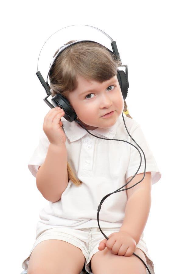 La fille écoute musique dans des écouteurs images libres de droits