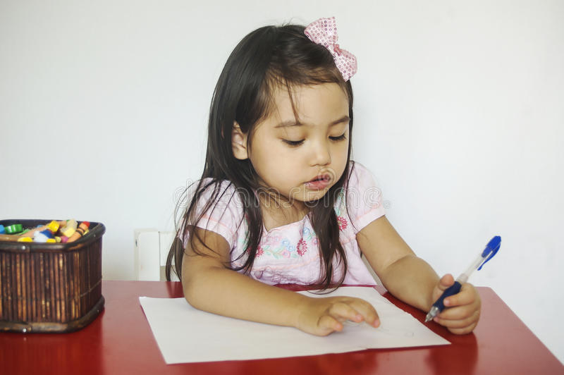 La fille écrit sur le papier photographie stock