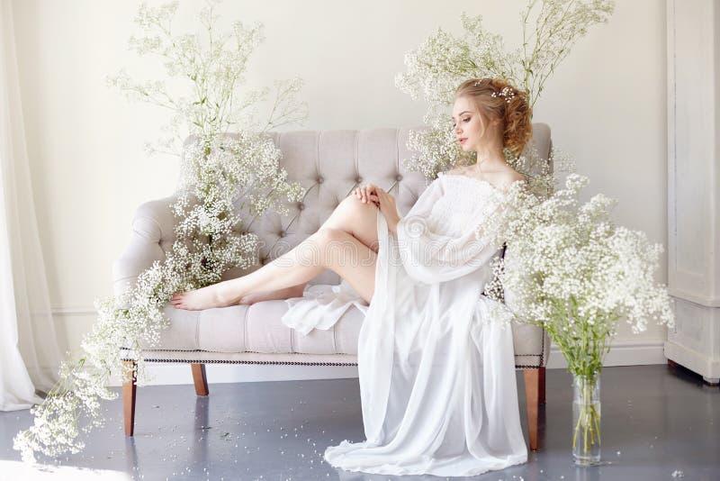 La fille écrit une lettre à son homme aimé, s'asseyant à la maison à la table dans une robe, une pureté et une innocence de lumiè photo libre de droits