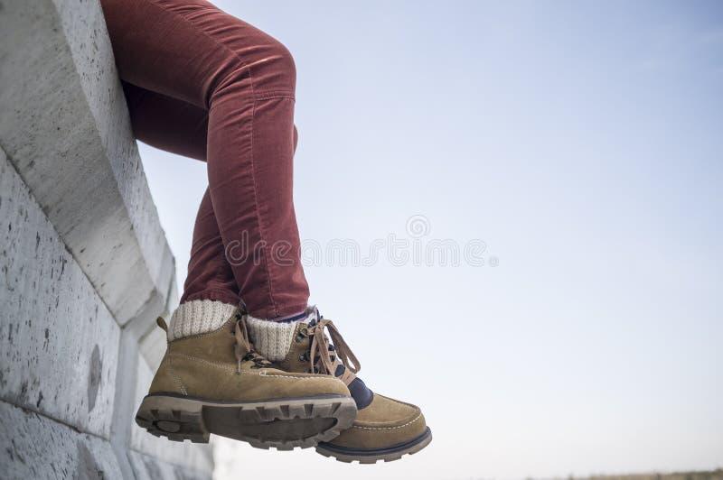 La fille élégamment habillée repose balancer et croiser ses jambes sur a photographie stock