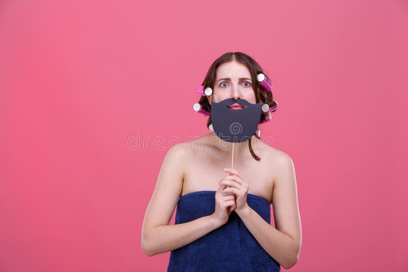 La fille émotive avec les rouleaux thermiques sur ses cheveux, enveloppés dans une serviette, tient une barbe sur un bâton et des photos stock