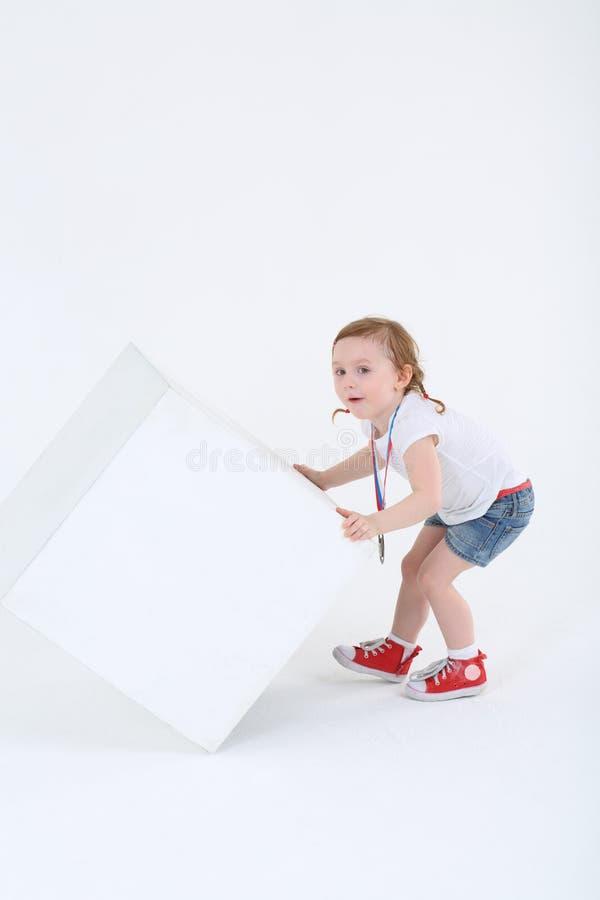 La fille étonnée peu avec la médaille sur le coffre renverse le cube images stock