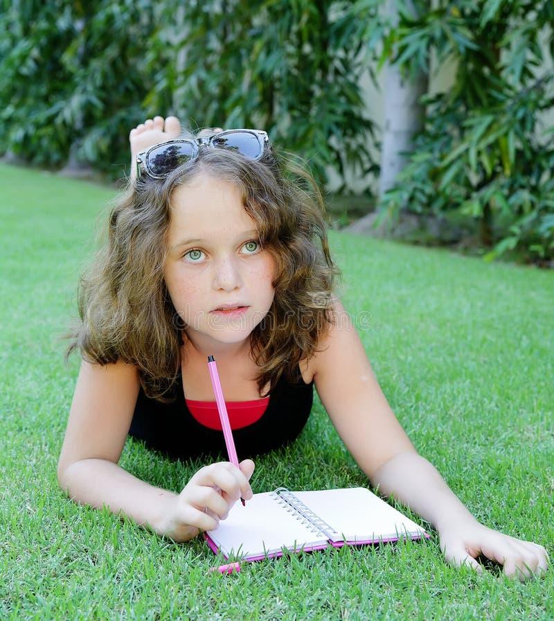 La fille 12 ans écrivent dans un cahier photo libre de droits
