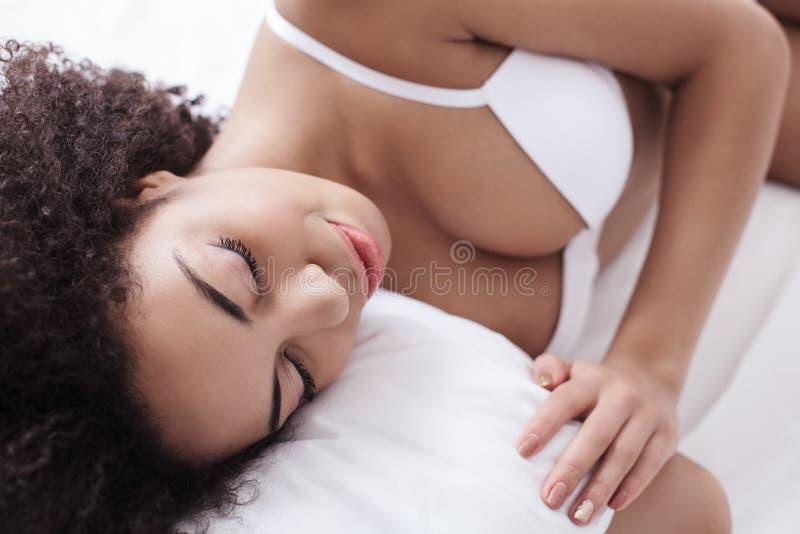 La fille africaine mignonne dort à la maison photo stock
