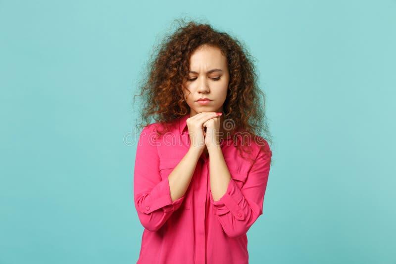 La fille africaine perplexe dans des vêtements sport roses regardant vers le bas, a mis l'appui vertical de main sur le menton d' photographie stock libre de droits