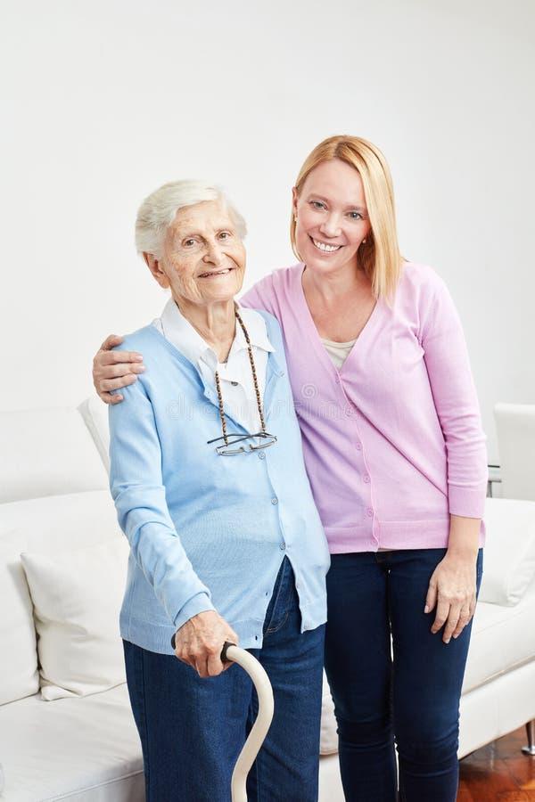 La fille aimante s'occupe du vieillard comme mère image stock