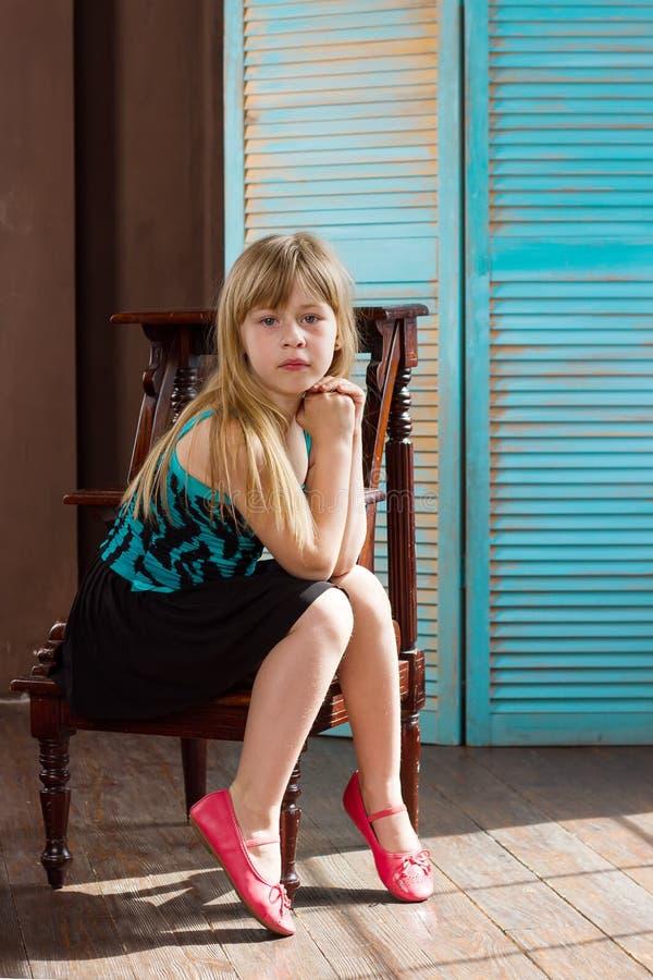 La fille 6 années dans une robe s'assied sur la chaise photo libre de droits