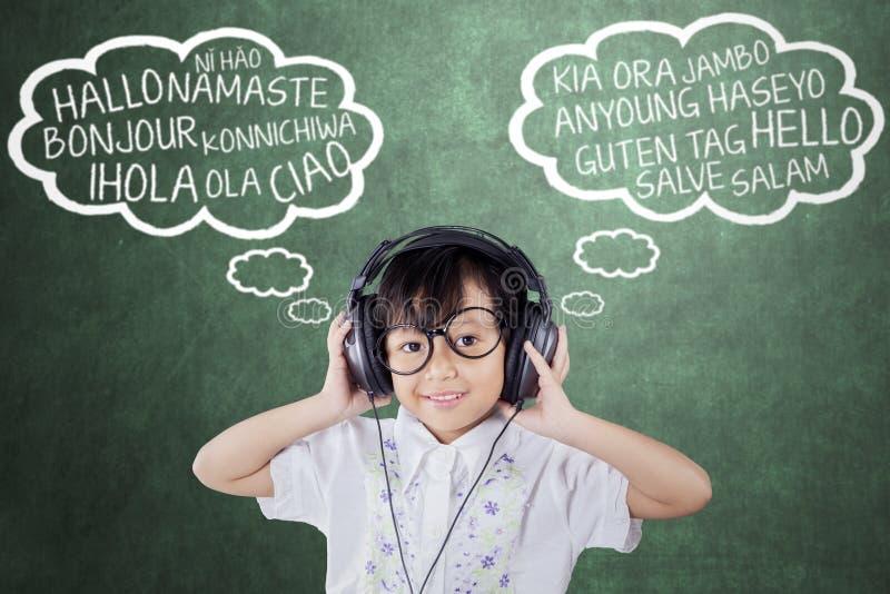 La fille apprend la langue étrangère avec des écouteurs images libres de droits