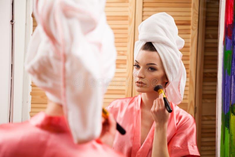 La fille après douche fait le maquillage image stock
