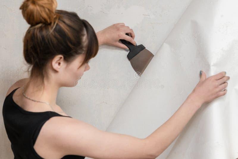 La fille arrache le vieux papier peint du mur en béton et tient une spatule photos libres de droits