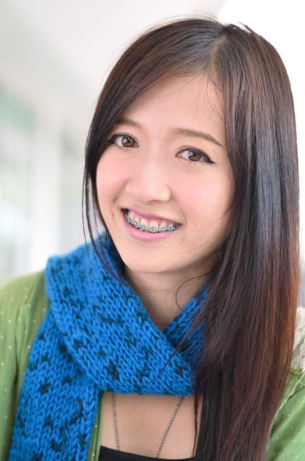 La fille asiatique d'étudiant est sourire et des dents de afficher photo stock