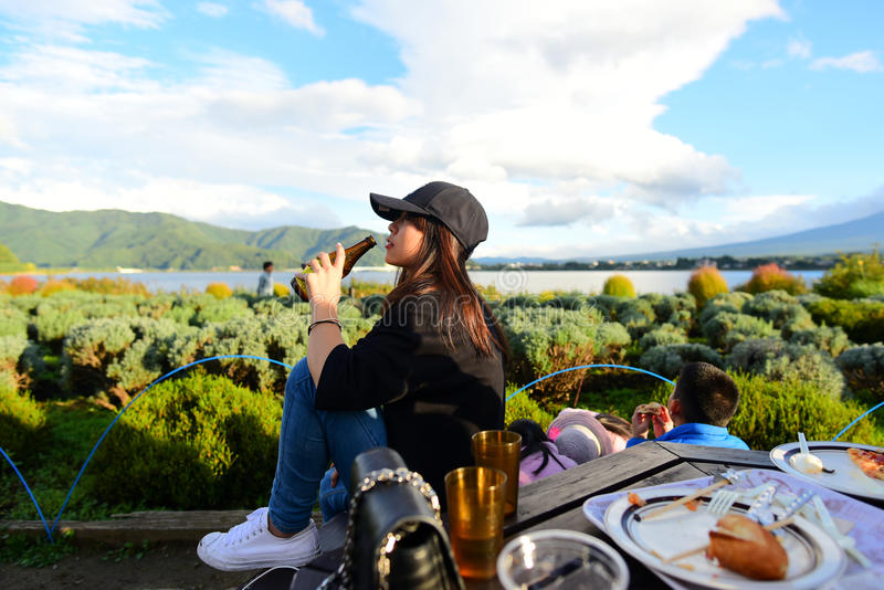 La fille asiatique d'adolescent apprécient et tenant la bouteille de bière images libres de droits
