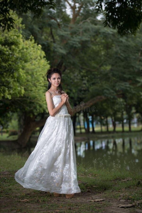 La fille asiatique dans la robe de mariage dans la forêt images libres de droits