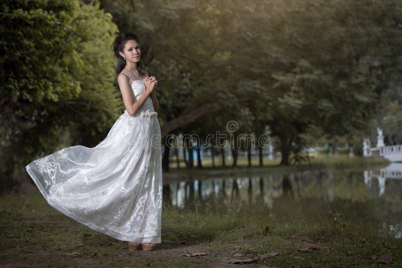 La fille asiatique dans la robe de mariage dans la forêt photographie stock