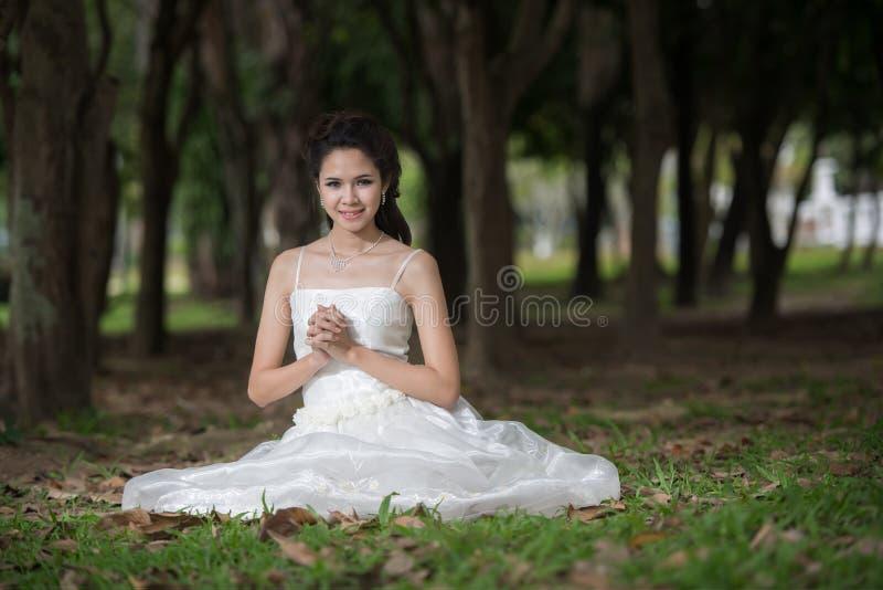 La fille asiatique dans la robe de mariage dans la forêt photos stock