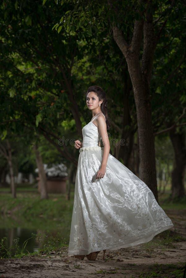 La fille asiatique dans la robe de mariage dans la forêt images stock