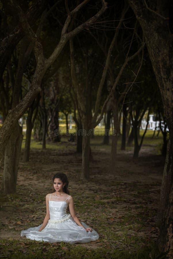 La fille asiatique dans la robe de mariage dans la forêt image libre de droits