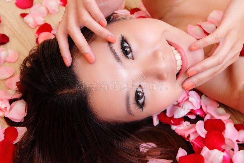 La fille asiatique de beauté souriant avec s'est levée photographie stock libre de droits