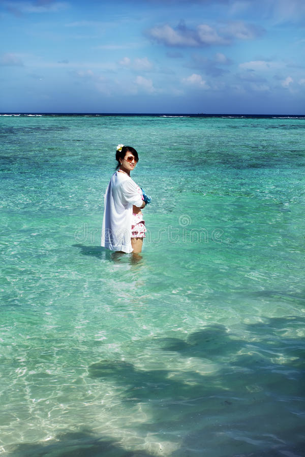 La fille asiatique de belle mode joue l'eau dans l'océan image stock