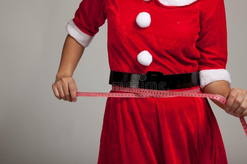 La fille asiatique de Noël dans des vêtements de Santa Claus suivent un régime avec la mesure photographie stock libre de droits