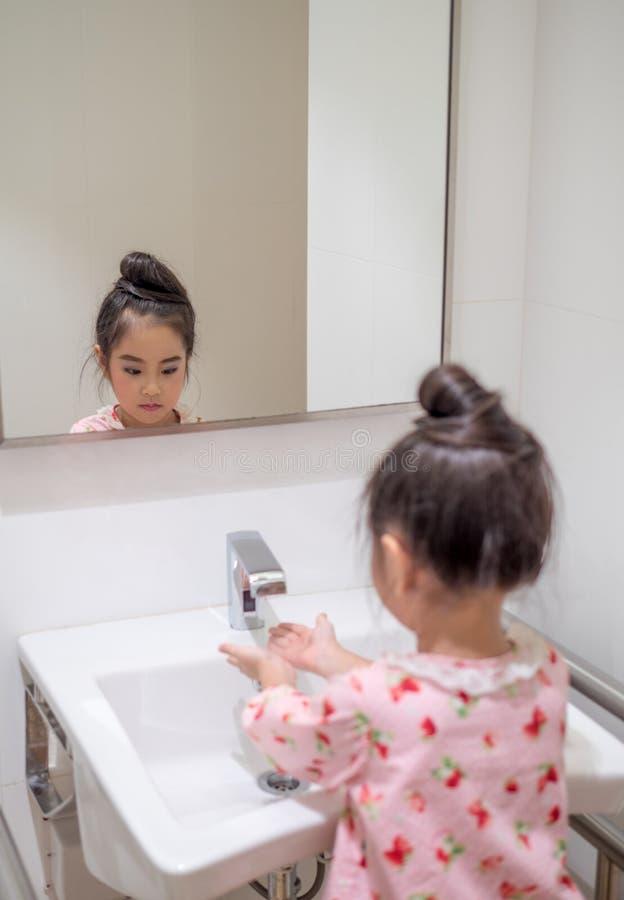 La fille asiatique de petit enfant se lavent la main photo stock